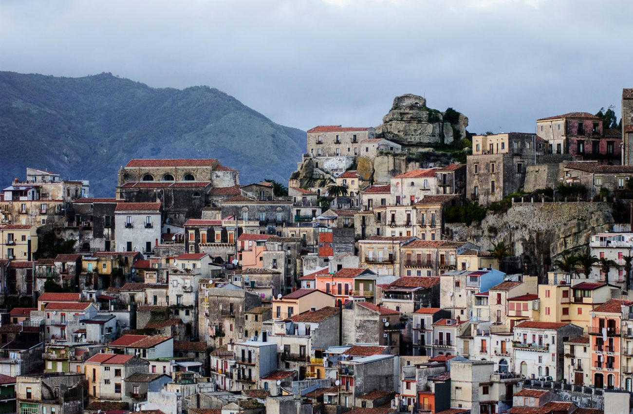 Colorful houses in Sicilian village with mountains in the background
