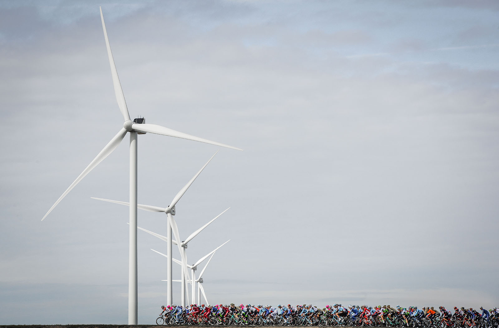 The Peleton passing some Windmills in Paris-Nice Cycling race