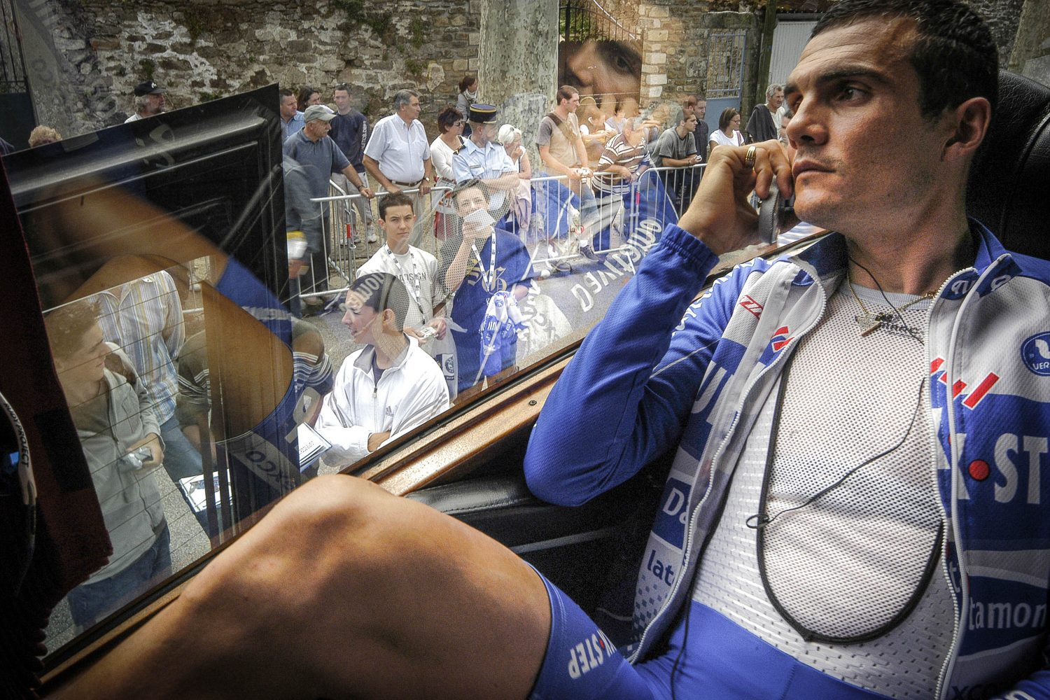 Virenque sitting in the bus speaking in his mobile phone and look at the crowd