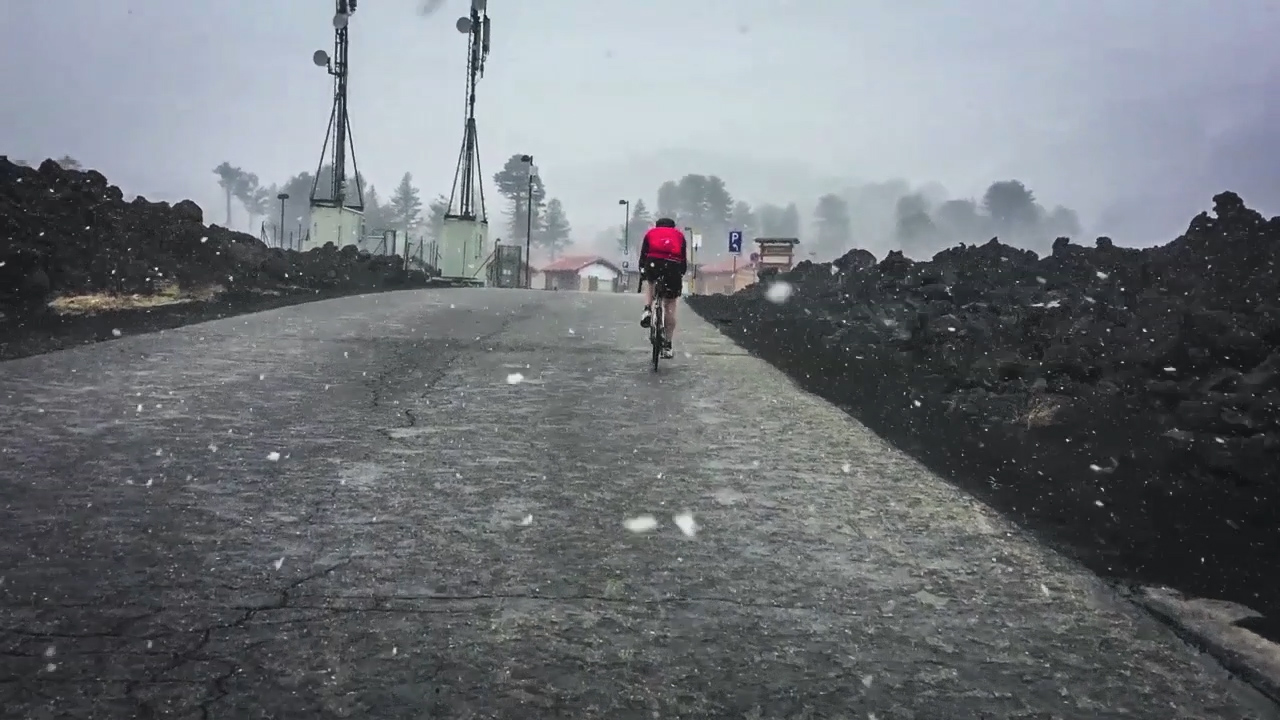 Cyclist on Etna in the snowstorm