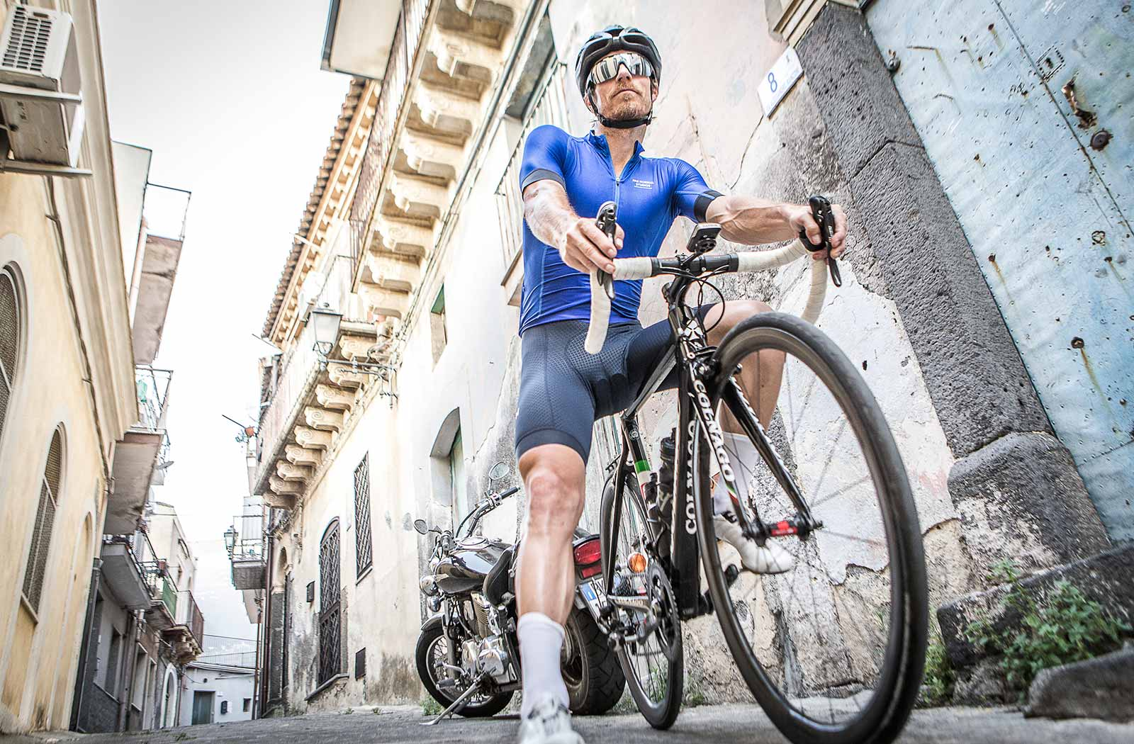 cyclist-standing-next-to-blue-door-in-pas-normal